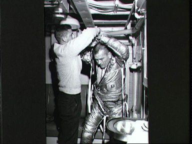 Astronaut Donald Slayton being assisted into his suit for egress training