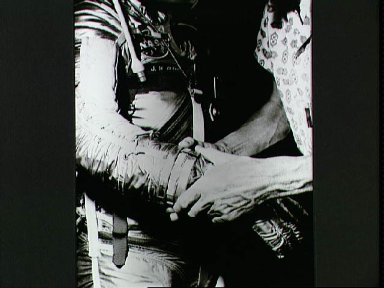 Astronaut John Glenn is fitted with space suit gloves during preflight
