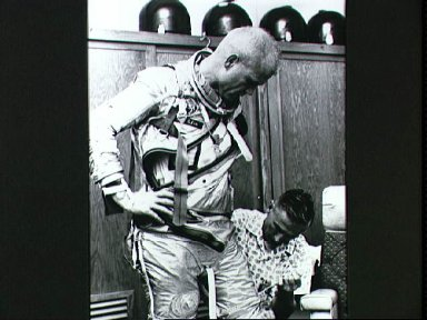 Astronaut John Glenn is fitted in his space suit during preflight training