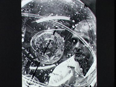 Astronaut John Glenn looks into a globe in the Aeromedical Laboratory