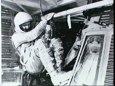 Astronaut John Glenn practices insertion into Mercury spacecraft