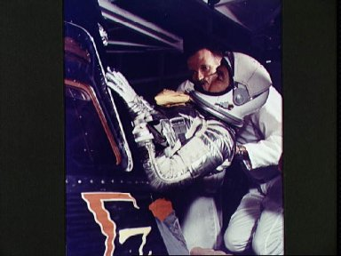 Astronaut Walter Schirra is assisted into his Sigma 7 spacecraft