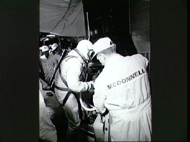Astronaut John Young assisted into Gemini spacecraft in white room