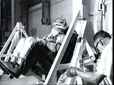 Astronaut Edward White being weighed and balanced in spacecraft seat