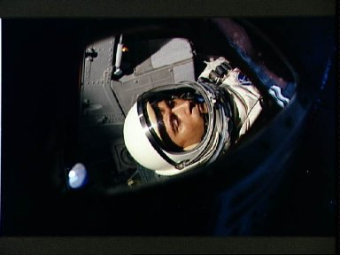 View of Astronaut John Young through spacecraft window prior to launch