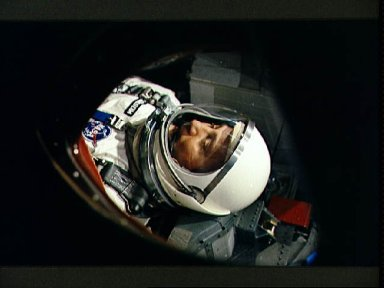View of Astronaut Virgil Grissom through spacecraft window prior to launch