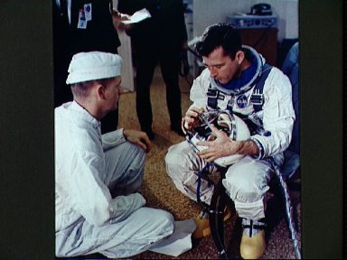 Astronaut John Young checks helmet during suiting operation prior to flight