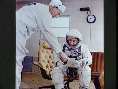 Astronaut Virgil Grissom looks at check list with suit technician