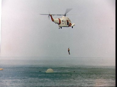 Astronaut Eugene Cernan hoisted aboard a helicopter during water egress