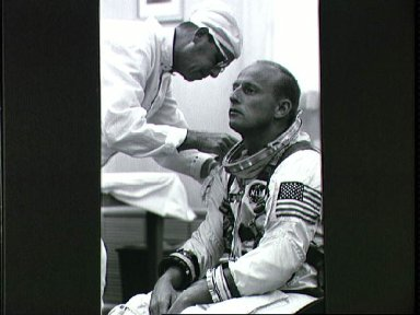 Astronaut Charles Conrad recieves help in suiting up before mission