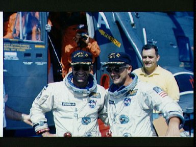 Astronauts Conrad and Gordon pose in front of recovery helicopter