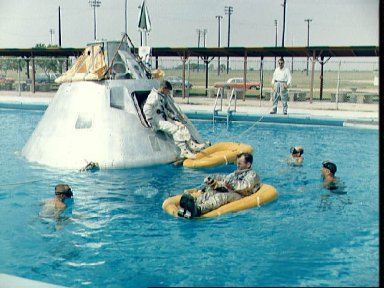 Crew of the first manned Apollo mission practice water egress procedures