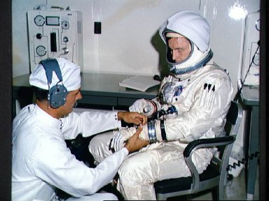 Astronaut Edward White receives help from technician during tests at KSC