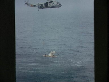 Member of Apollo 7 crew hoisted to helicopter during recovery operations