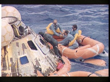 Navy swimmer assists Apollo 12 crew during recovery operations