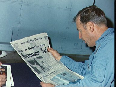 Astronaut James Lovell reads newspaper account of Apollo 13 safe recovery
