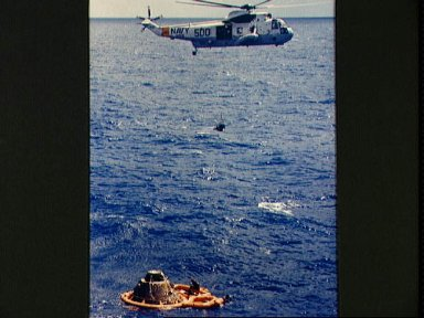 Astronaut Stuart Roosa hoisted inside recovery net to Navy helicopter