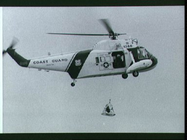 Astronaut Charles Duke hoisted up to Coast Guard helicopter during training