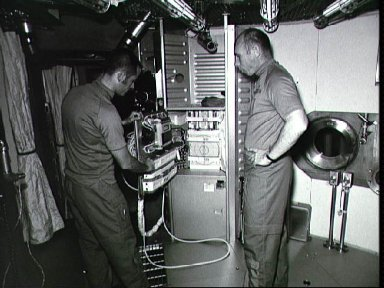 Astronauts Crippen and Thornton stand with off-duty recreation equipment