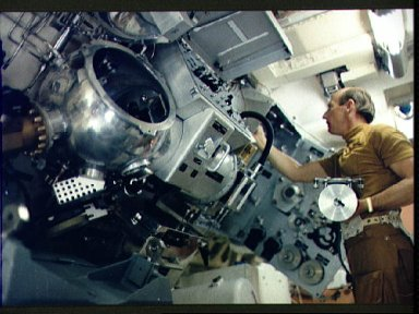 Astronaut Charles Conrad takes items from materials processing storage area