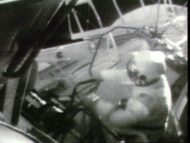 Astronaut Jack Lousma hooks up cable for rate gyro six pack during EVA