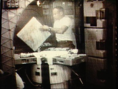 Astronaut Jack Lousma looks at map of Earth in ward room of Skylab cluster