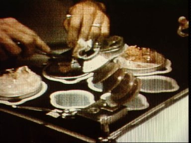 View of Jack Lousma's hands using silverware to gather food at food station