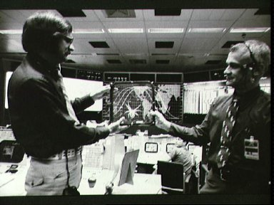 Personnel in Mission Control examine replica of spider habitat from Skylab 3