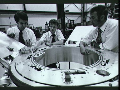American and Soviet engineers examine Soyuz docking system prior to tests