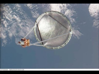 Following its deployment from the Space Shuttle Endeavour, the Spartan 207/Inflatable Antenna Experiment (IAE) payload is backdropped over clouds and water.