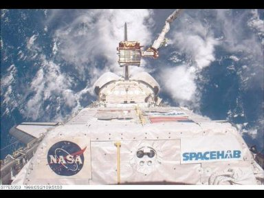 The Spartan 207 free-flyer is held in a low-hover mode above its berth in the Space Shuttle Endeavour's cargo bay in the grasp of the Remote Manipulator System (RMS).