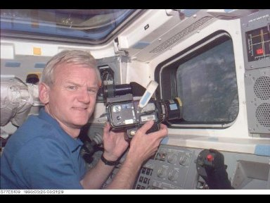 Astronaut John H. Casper, commander, pauses during a photography session on the aft flight deck of the Space Shuttle Endeavour.
