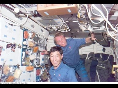 Astronauts Mario Runco, Jr. and Andrew S. W. Thomas, both mission specialists, pose for photo while in the mid-deck of the Earth-orbiting Space Shuttle Endeavour.