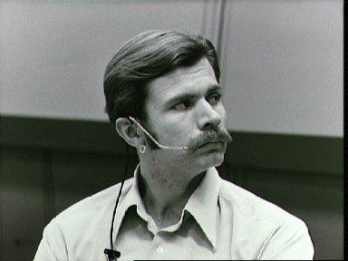 Mission controller Donald R. Puddy, wearing headset, in Mission Control