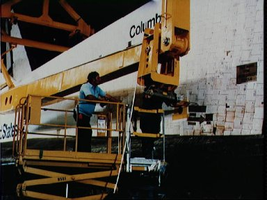 Workers in the VAB move sling into place to lift Columbia to mobile launcher