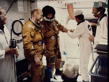 Astronaut Lousma is assisted with a glove adjustment to flight suit