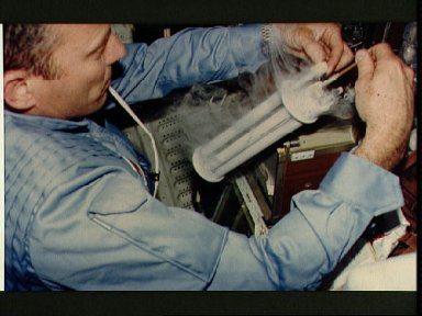 Commander Lousma works with EEVT experiment and cryogenic tube on aft middeck