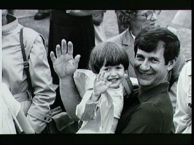 Astronaut Terry Hart holds son and waves to camera after return STS-3