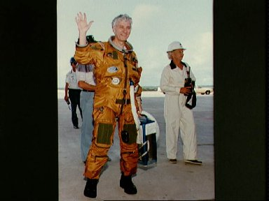 Astronaut Hartsfield wearing pressure suit waves to photographers