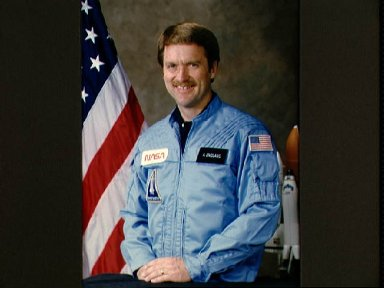 Portrait of astronaut Anthony W. England, dressed in blue flight suit