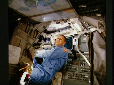 Astronaut Robert F. Overmyer behind the pilot's seat on the flight deck