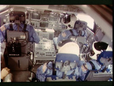 STS-6 crewmembers go through a training exercise in the shuttle mock-up