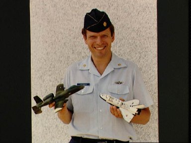 Byron Lichtenberg with models of A-10 aircraft and shuttle with payload