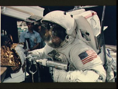 Astronaut Joe Allen simulates use of a power tool in space during training