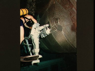 Astronauts Fisher and Van Hoften work with mockup of the Syncom/LEASAT
