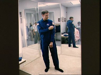 STS-26 Pilot Covey checks flight suit sleeve decal during wardrobe fitting