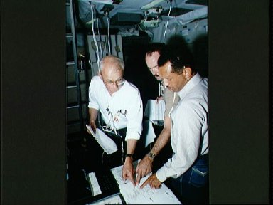 STS-31 crewmembers review checklist with instructor on JSC's FB-SMS middeck