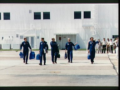 STS-26 crewmembers walk across parking apron to T-38s at Ellington Field