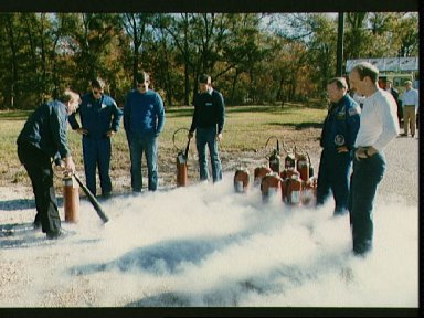 Fire/security staff member instructs STS-29 crew on fire extinguisher usage