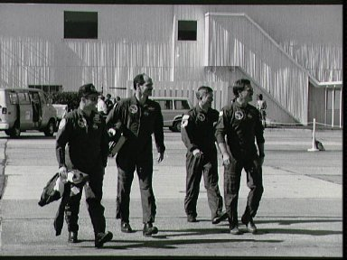 STS-27 crewmembers walk across parking apron to T-38s at Ellington Field